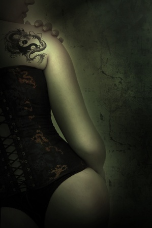 Sexy woman with corset and dragon tattoo in a grunge background photo