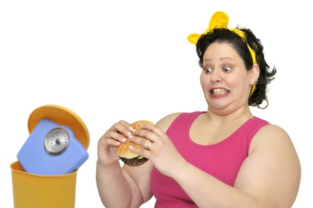 Large girl with hamburger and weight scale in the garbage bin photo