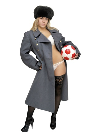 Sexy girl in russian army greatcoat and lingerie holding a soccer ball isolated in white photo