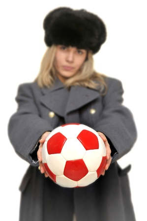 Out of focus  girl in russian army greatcoat and lingerie holding a soccer ball isolated in white photo