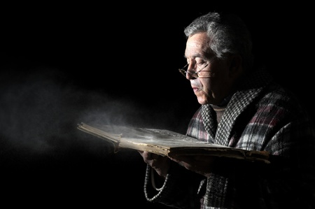 Senior man blowing dust of  a very old book isolated in black photo