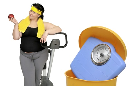 Large woman with an apple and a weight scale in the garbage photo
