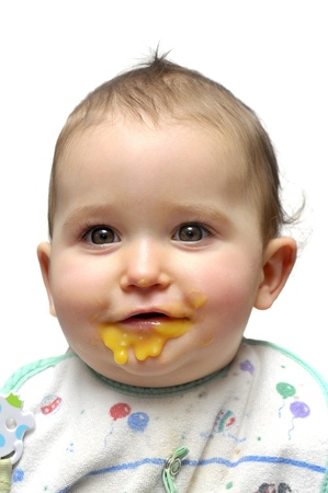 baby girls smiley face: Portrait of a young baby eating
