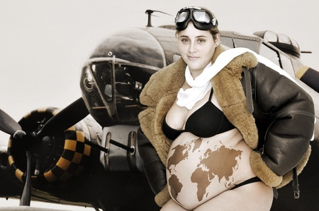 Pregnant woman with pilot jacket and world map in her belly and a bomber as background photo