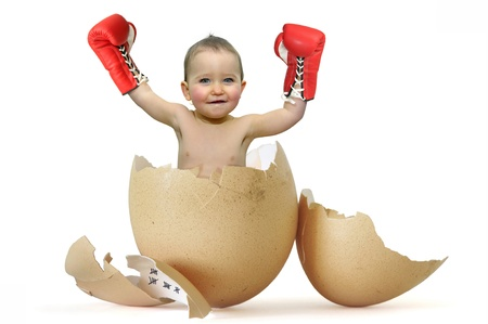 Beautiful baby with boxing gloves breaking the egg photo