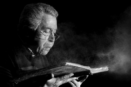 Senior man blowing dust of  a very old book in black & white photo