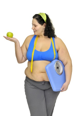 Large girl with apple and weight scale isolated in white Stock Photo - 8993491