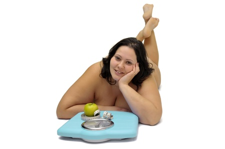 Beautiful nude large girl with weight scale isolated in white photo