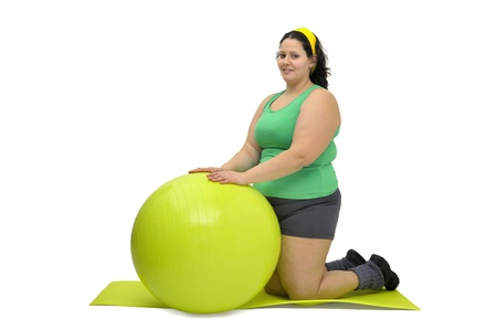Large girl exercising with big fitness ball isolated in white photo