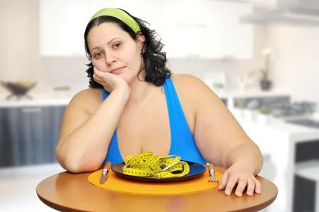 donne obese: Grande ragazza mangiando un nastro di misurazione