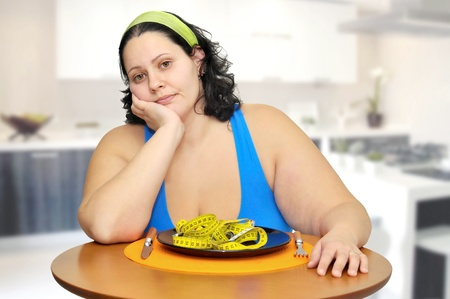 dieting: Large girl eating a measuring tape