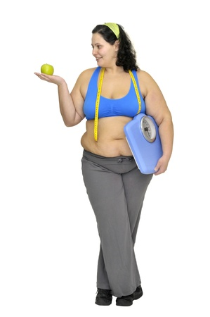 Large girl with apple and weight scale isolated in white photo