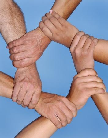 mani unite: Mani umane in un forte legame contro un cielo blu profondo Archivio Fotografico