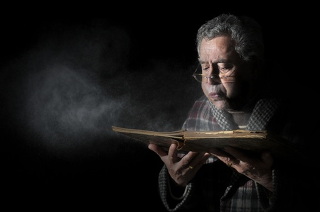 black history: Senior man blowing dust of  a very old book isolated in black Stock Photo