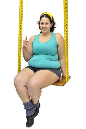 mujeres gordas: Ni�a grande en un columpio hecho de la cinta m�trica Foto de archivo