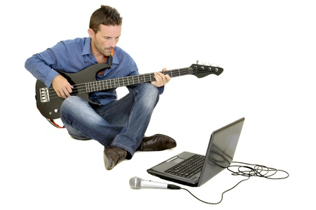 computer model: Young man playing guitar with a laptop Stock Photo