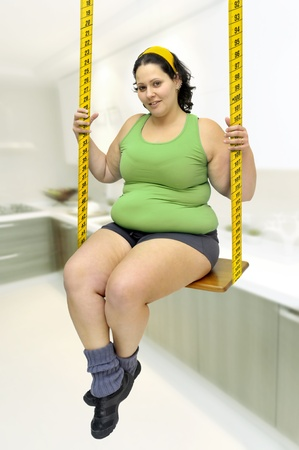 Large girl in a swing made of measuring tape  photo
