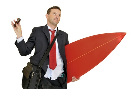 celphone: Young businessman with surf board recieving a call from the office
