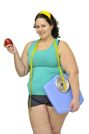 Large girl with weight scale and apple isolated in white photo