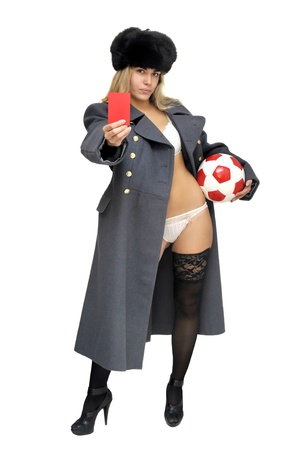 Sexy girl in russian army greatcoat  holding a soccer ball and a red card isolated in white photo