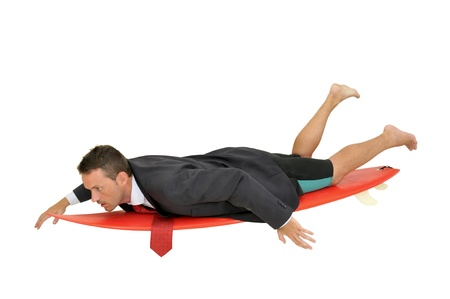 Young businessman laying in a surf board with laptop photo