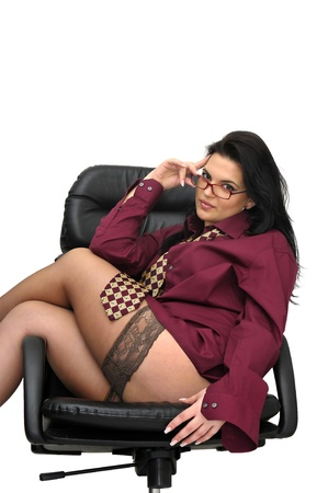 Sexy businesswoman in a chair with tie and stockings isolated in white Stock Photo