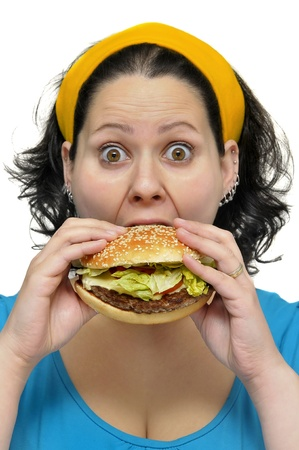 Large girl eating a hamburger isolated in white Stock Photo