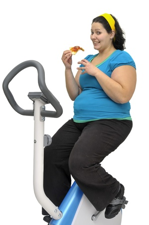 Large girl exercising and eating a pizza slice isolated in white photo