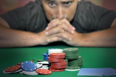 gambling: Stressed man in a poker table gambling Stock Photo