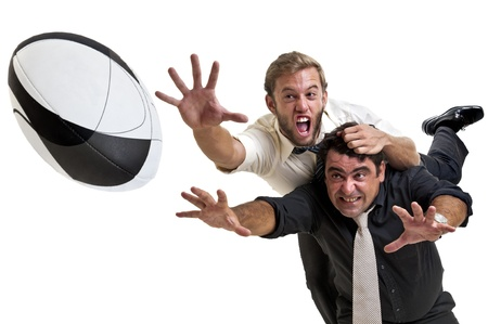 Les hommes d'affaires jouant au rugby isolées en blanc