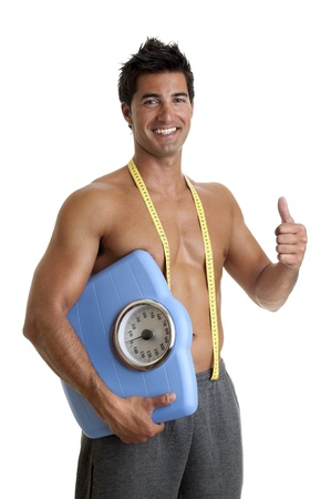 Muscular young man with weight scale Stock Photo