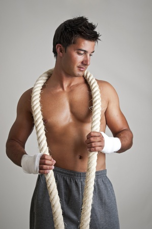 Muscular boxer posing with rope photo
