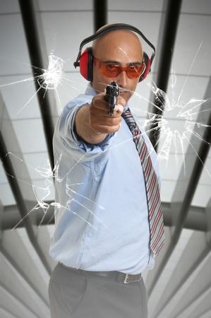Man with gun shooting through glass window photo
