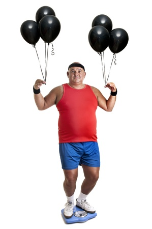 Large fitness man with weight scale and balloons isolated in white photo