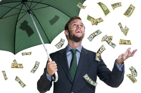 Young businessman with umbrella and money falling from the sky