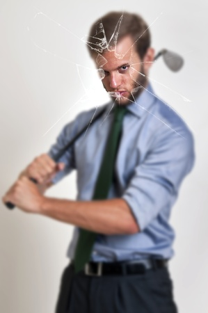 Businessman with golf club through a broken glass photo