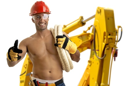 Strong build construction worker with big machine in the background photo
