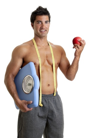 Muscular young man with apple and weight scale photo