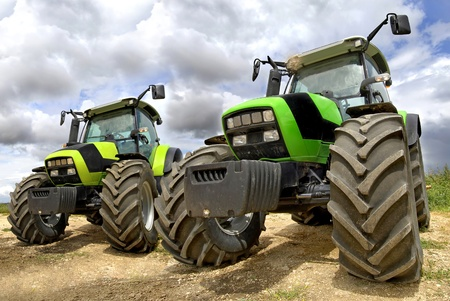 Green tractors in the field with a cloudy sky