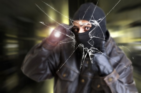 Burglar with flashlight over a broken glass Stock Photo