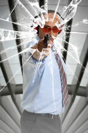 Man with gun shooting through glass window Stock Photo - 11268939
