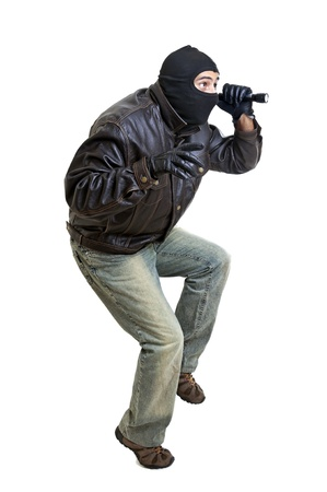 Burglar with flashlight isolated in white