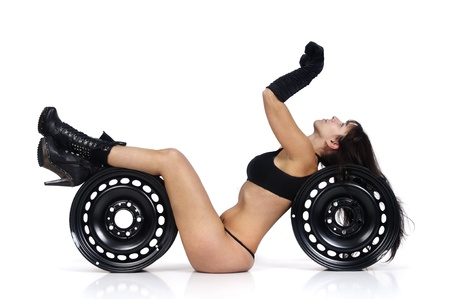 Sexy worker posing against a white background with black wheels photo