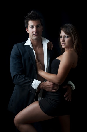 Sexy young couple isolated in black photo