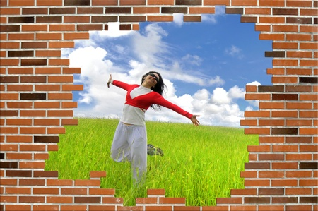 Woman jumping high in a green field with a scarf with a brick wall in the foreground photo