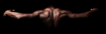 Beautiful and muscular black man's back in dark background photo