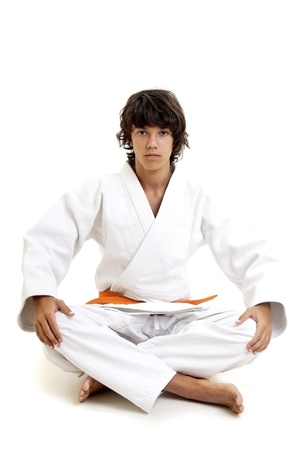 karate boy: Young fighter posing against a white background