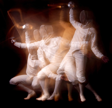 Male fencer isolated in a dark background photo