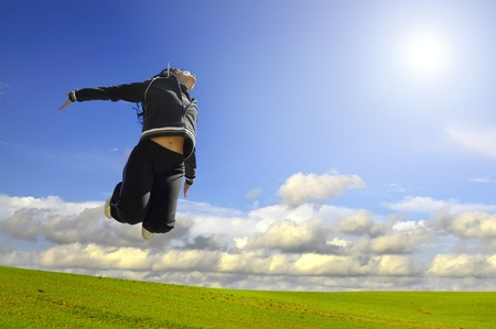 Woman jumping high in a green field photo