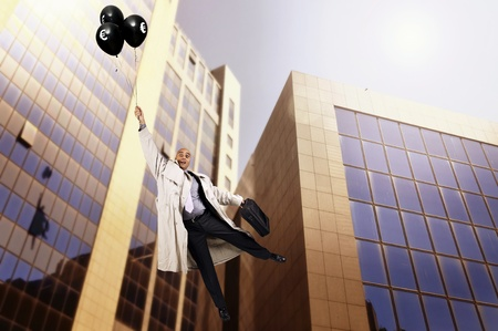 Businessman holding a group of black balloons photo